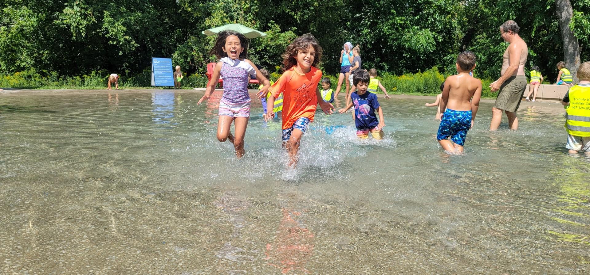 kids running through High PArk Toronto wading pool