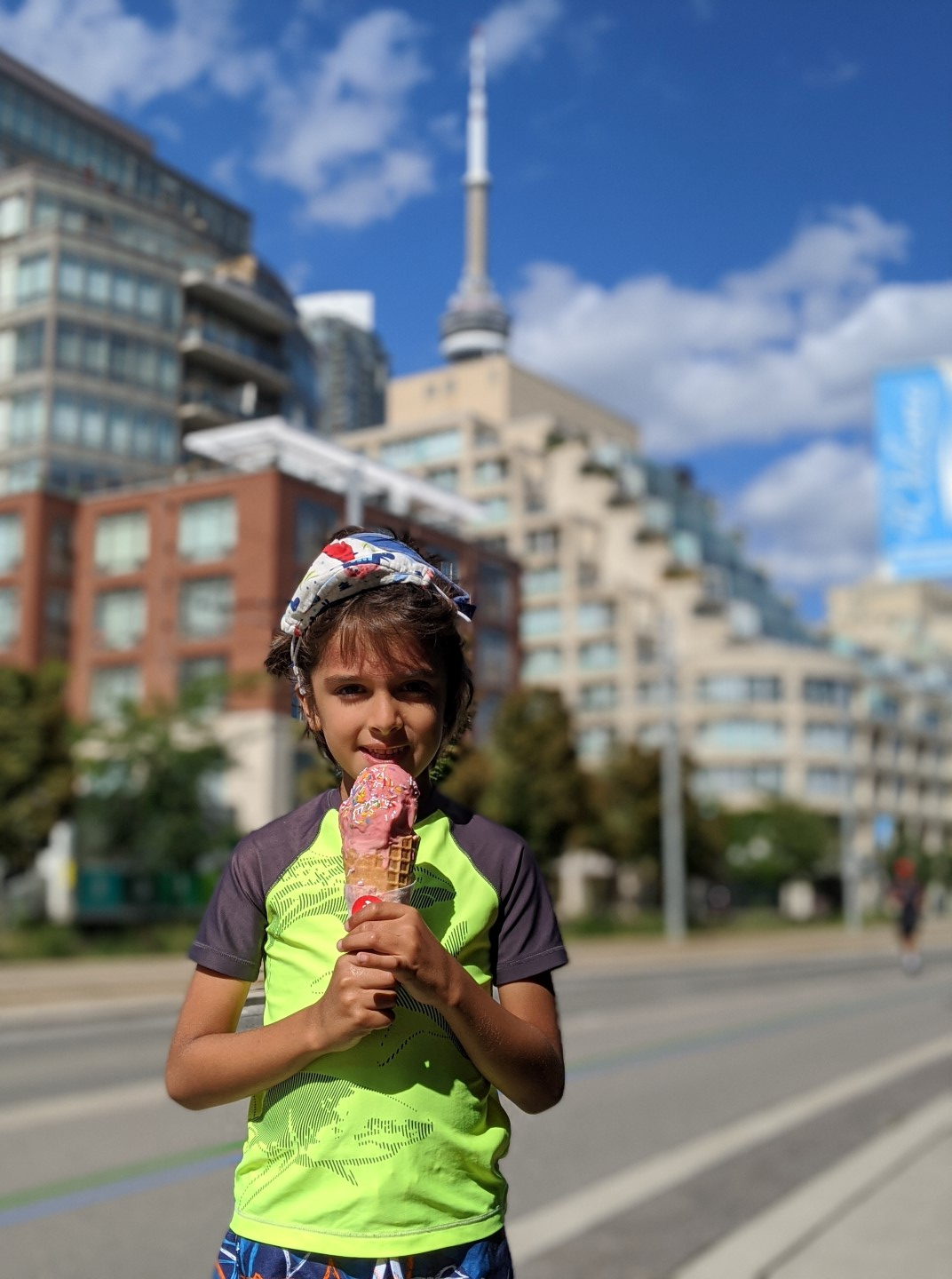 Boy in front of CN tower eating ice cream Toronto's Waterfront
