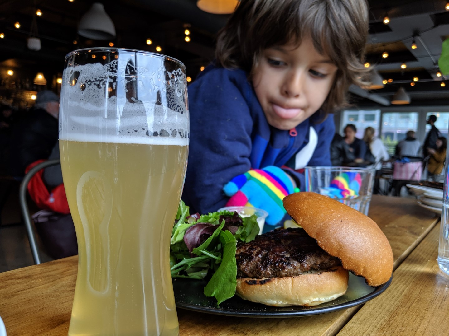 boy with tongue out in front of burger and beer