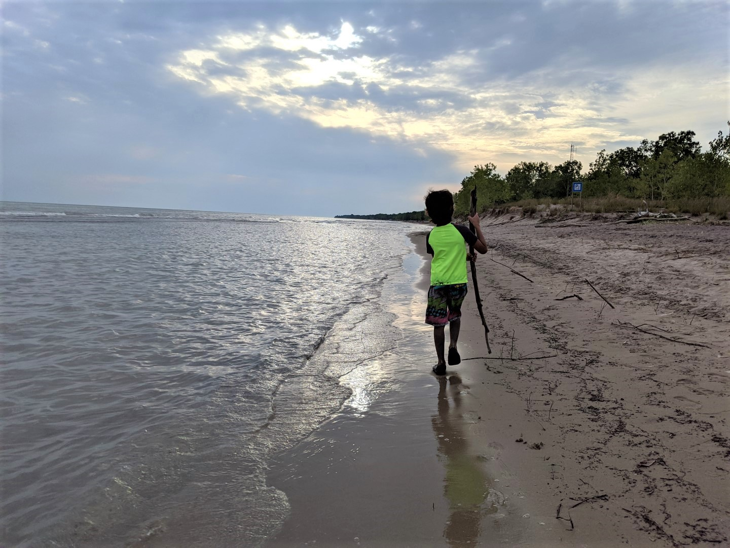 boy holding stick at Long Point Beach in Ontario at Sunset