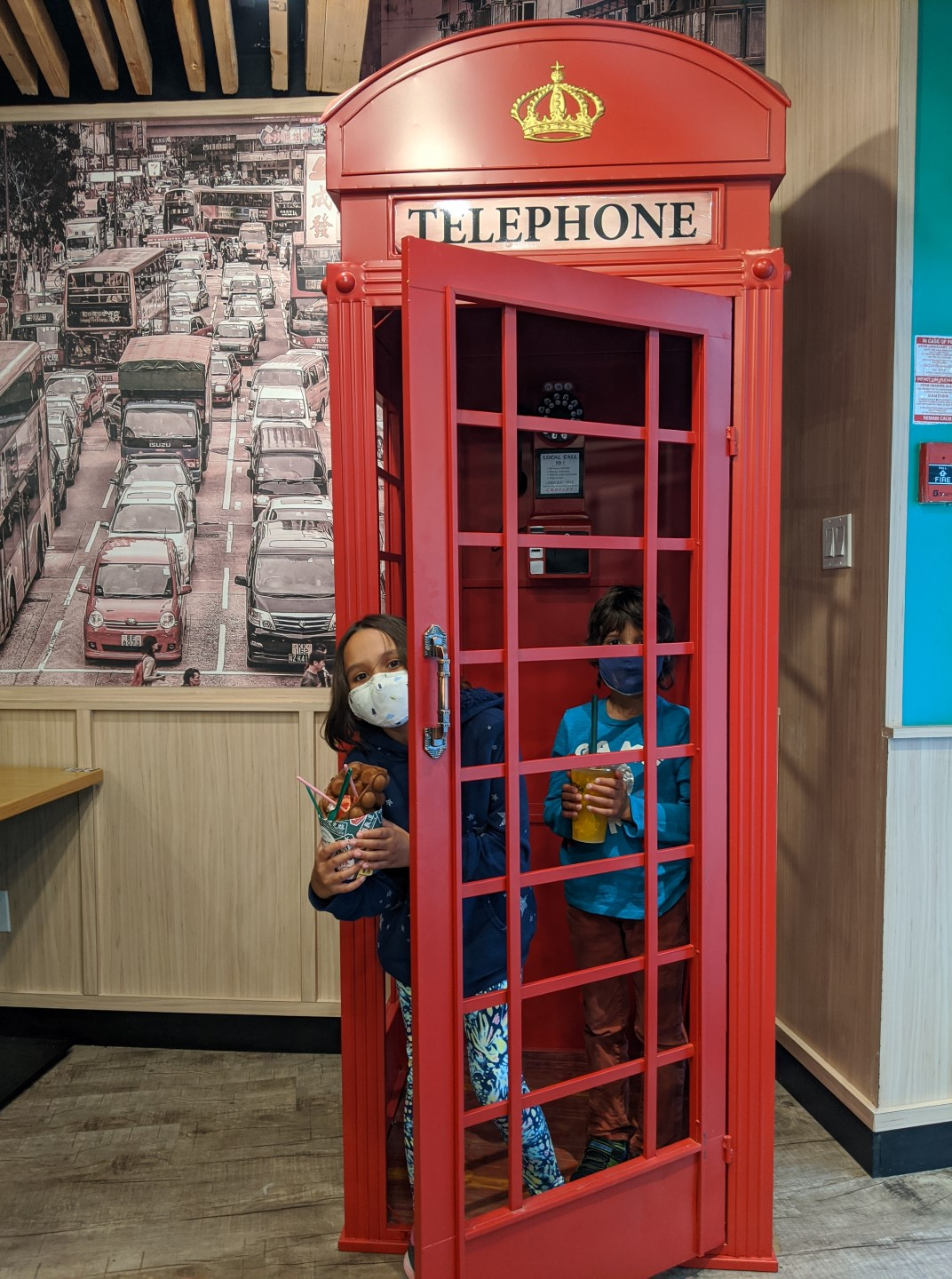 kids in telephone booth at dessert shop