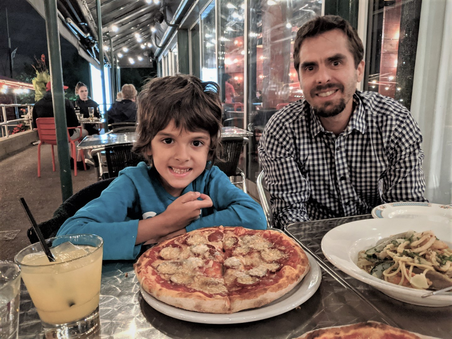 son and father in front of pizza