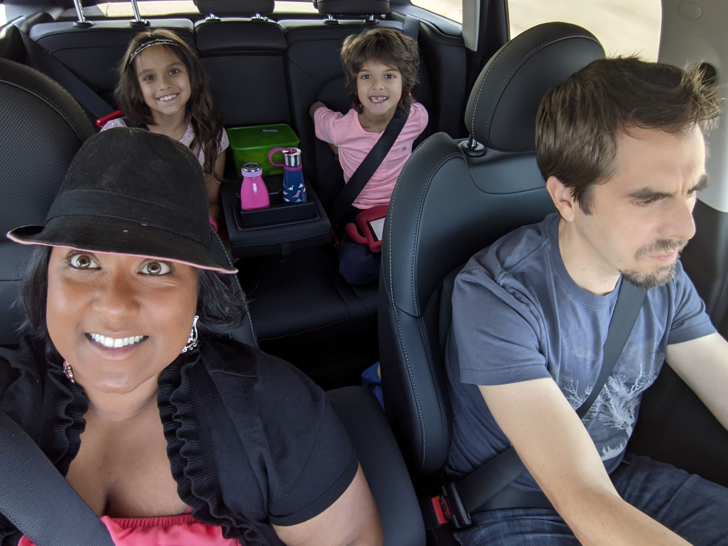 mom, dad and two kids in car for road trip