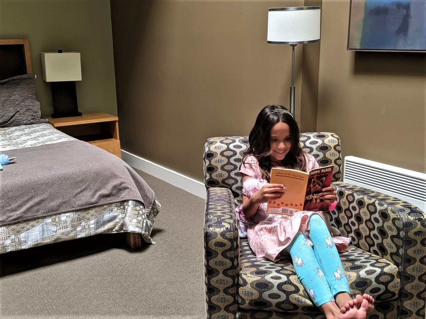 Girl reading book on couch with bed in background at Bentley's Loft Stratford