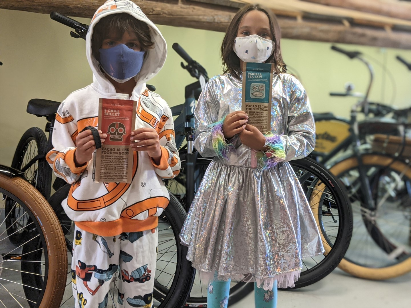 masked kids holding chocolate with bikes