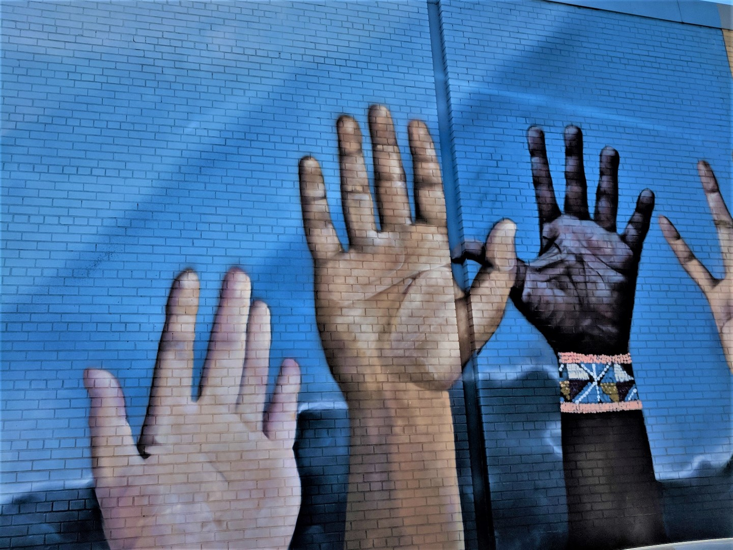 street art of hands on blue wall