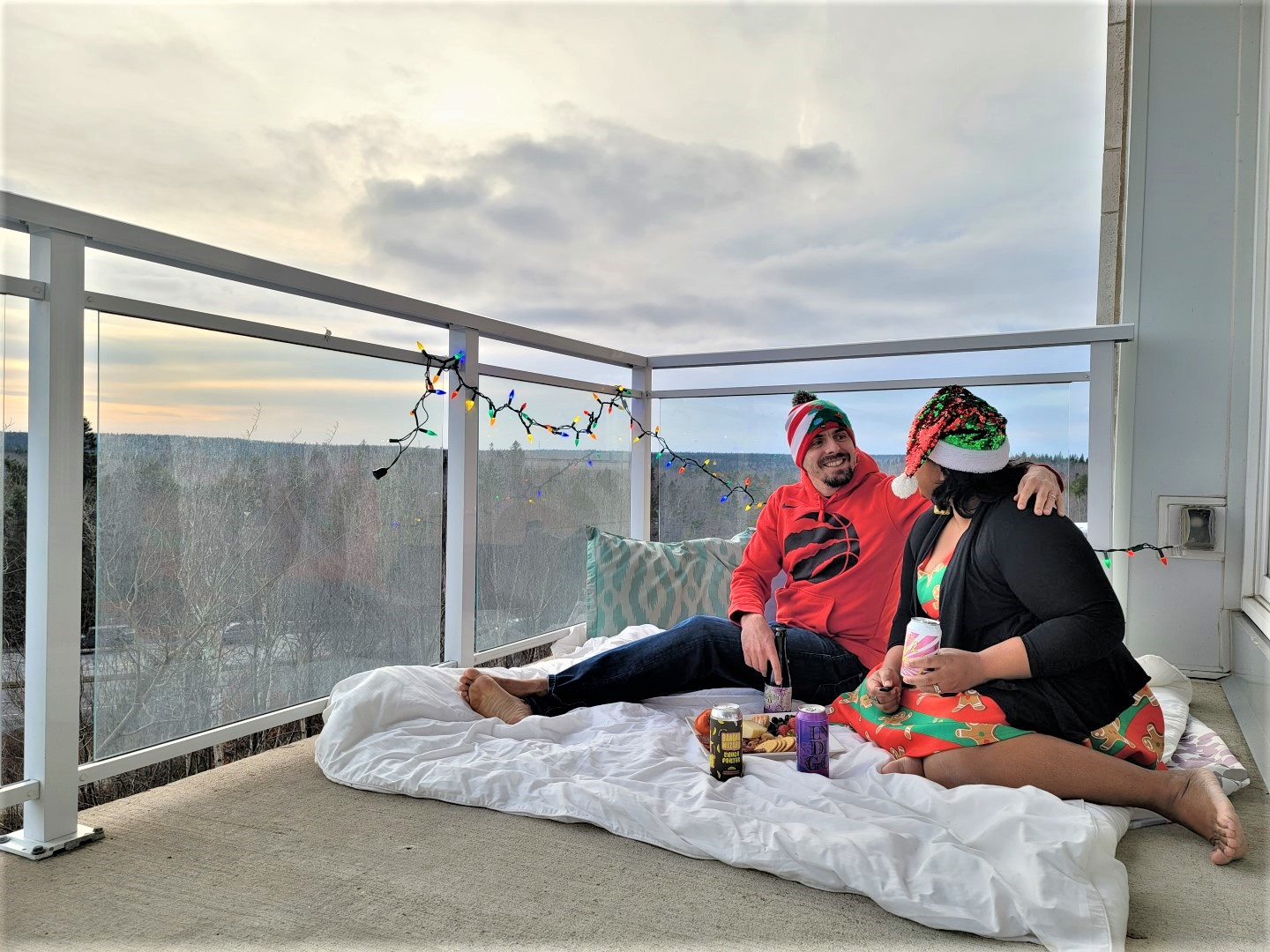 mixed couple on balcony with Christmas clothes