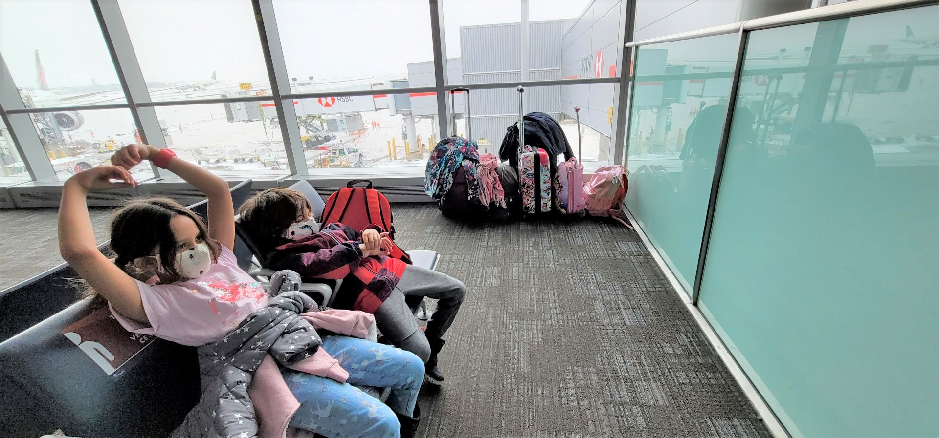 masked kids seated at Toronto pearson airport