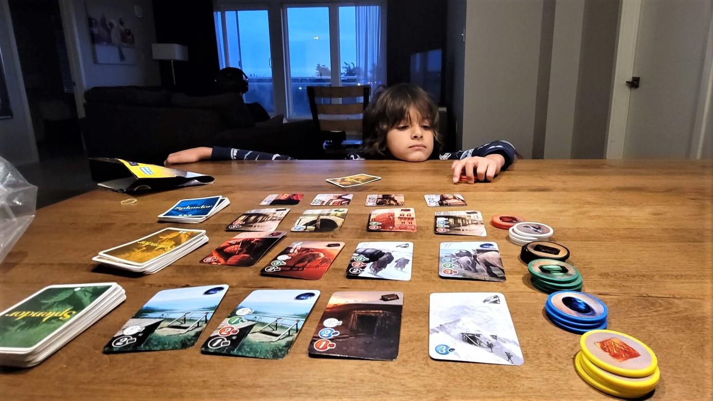 boy looking at Splendor board game