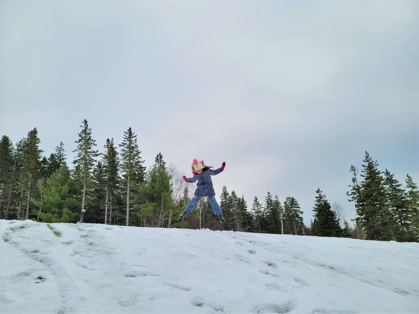 Girl jumping on snow hill in Nova Scotia