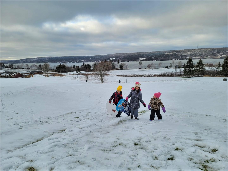 kids walking up a snow hill in Cape Breton