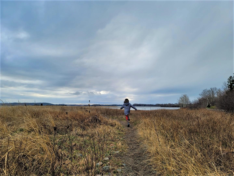 Girl in winter jacket running at Mahoney's Beach