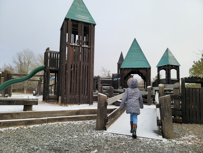 girl running through big wooden playground in Nova Scotia