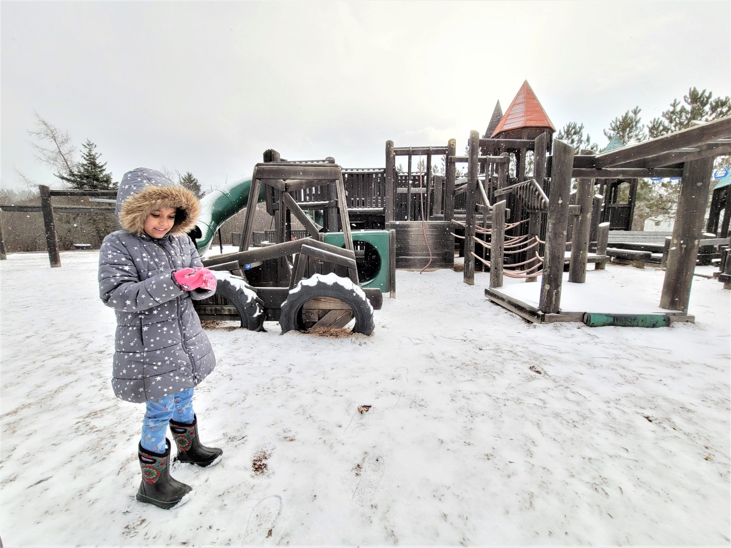 girl in snow covered big wooden playground