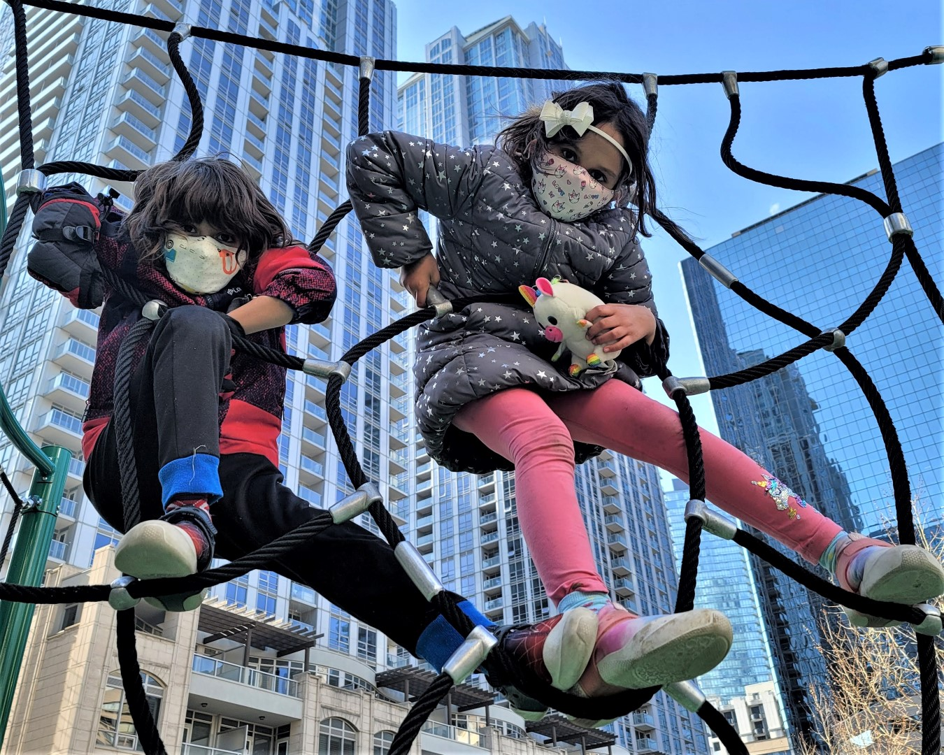 masked kids playing in front of Toronto skyscrapers