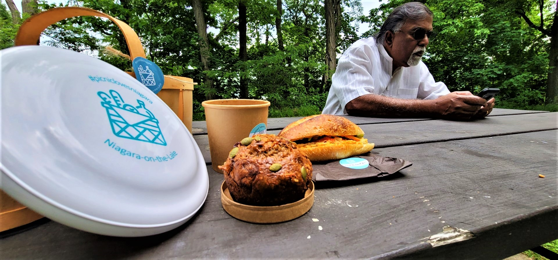 Elderly gentleman on phone at picnic table with frisbee and sandwich