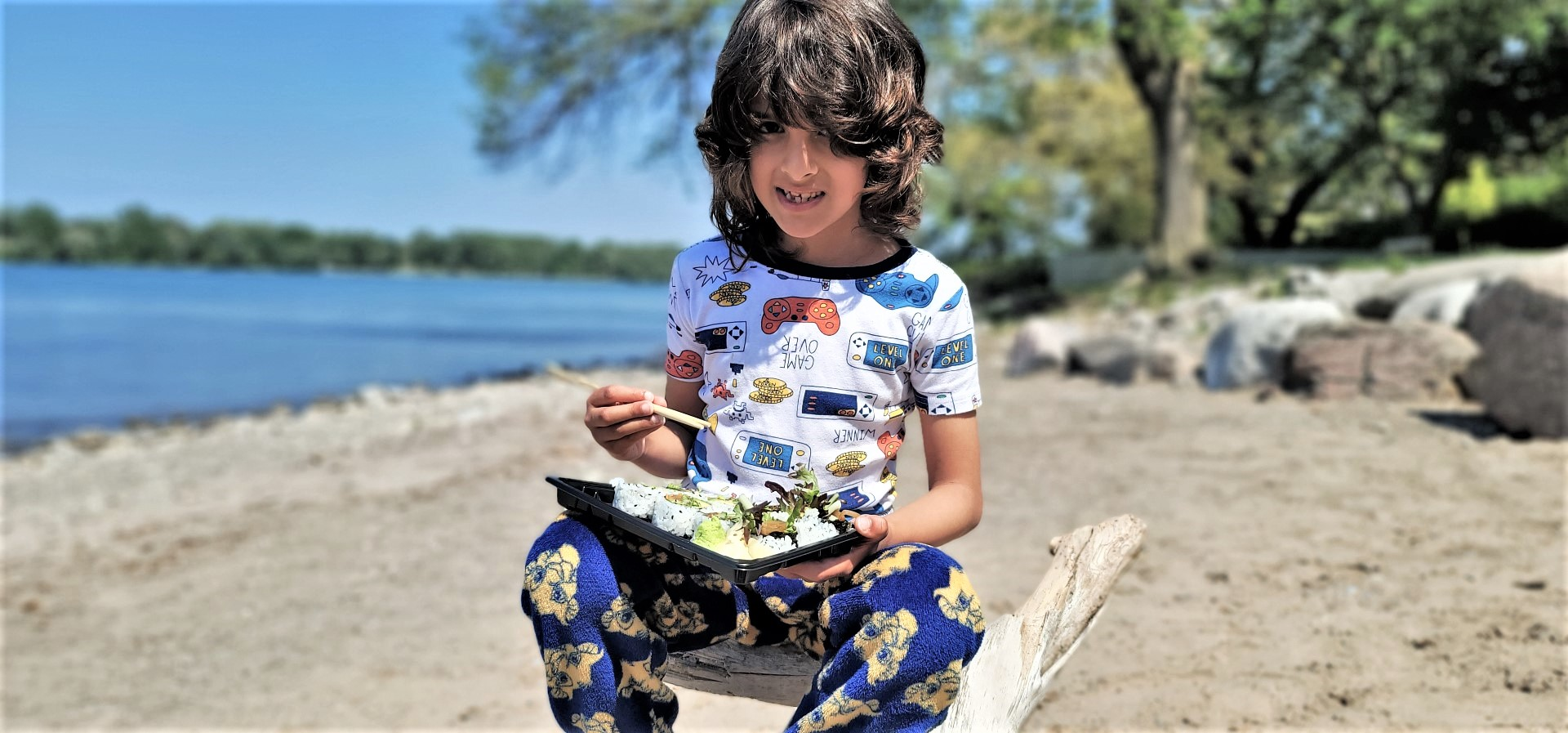 boy with long hair seated at beach eating sushi