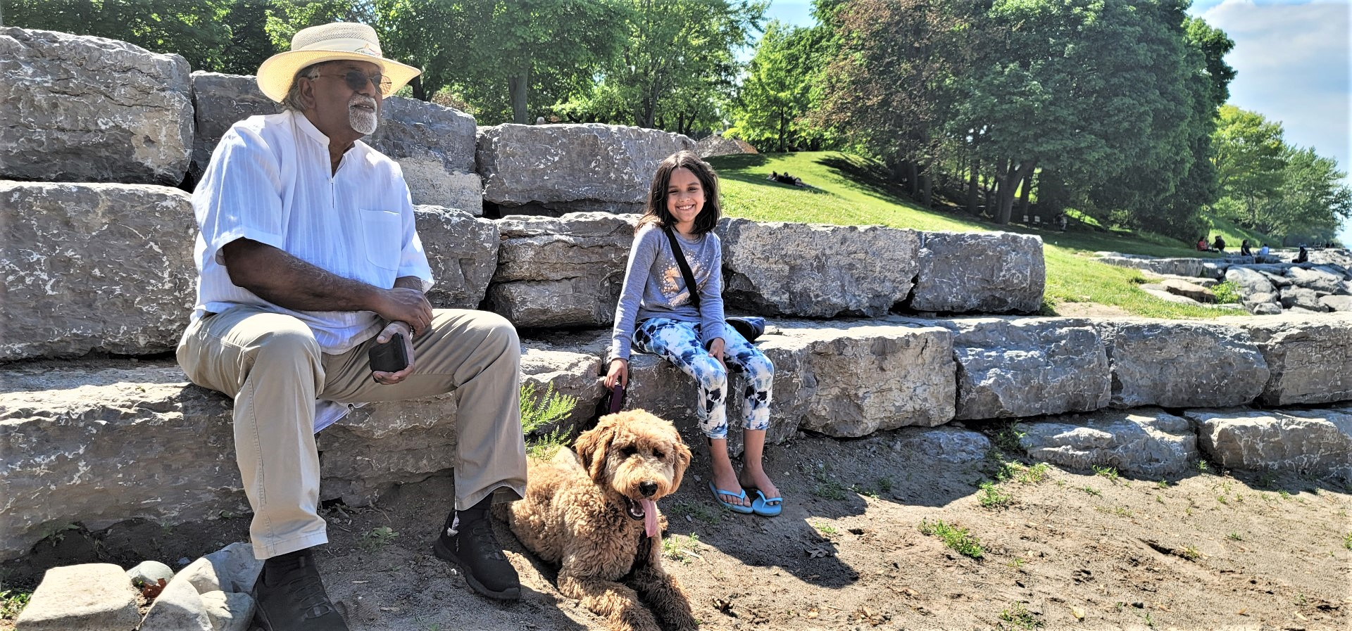 grandfather wearing hat seated on rocks with granddaughter and golden doodle