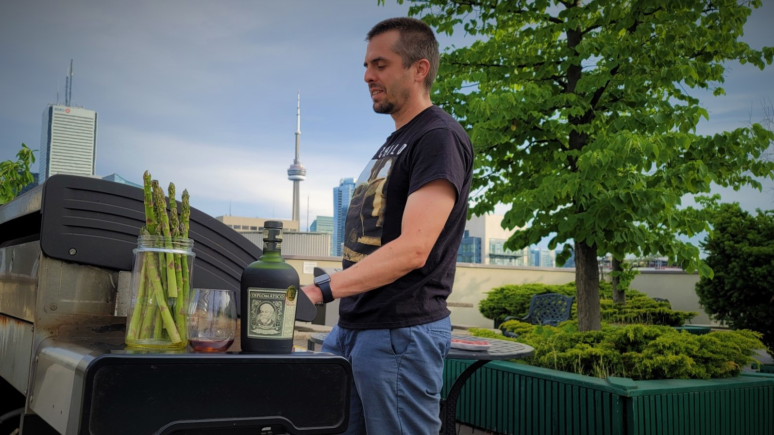 Man grilling with rum and asparagus. CN tower condo in background.