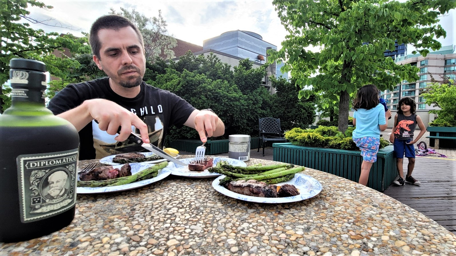Man cutting steak with bottle of rum on table