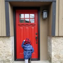 Boy in front of red door