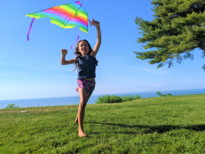 girl flying rainbow kite
