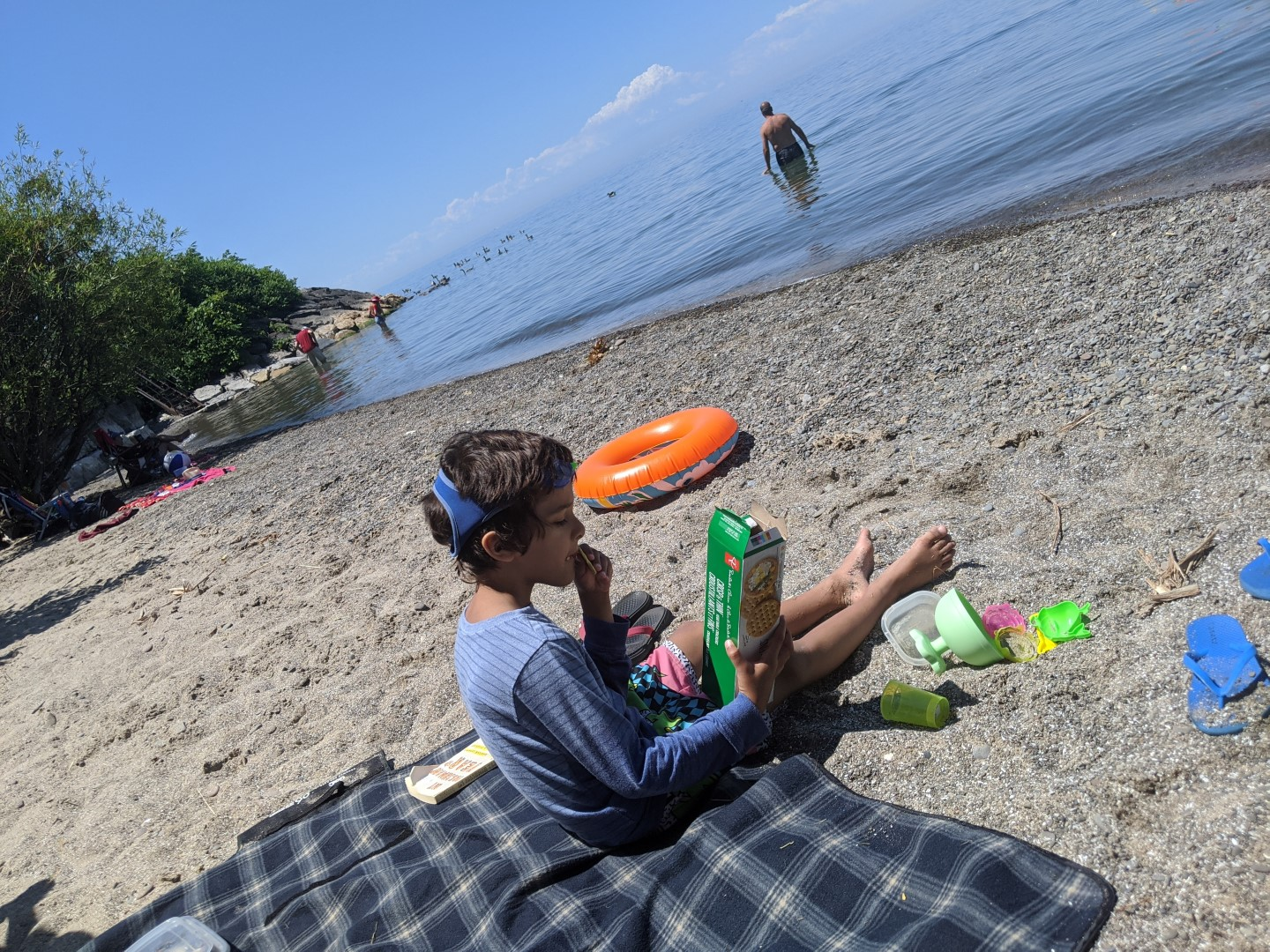 boy sitting on beach sand with crackers in hand and orange floatie on side