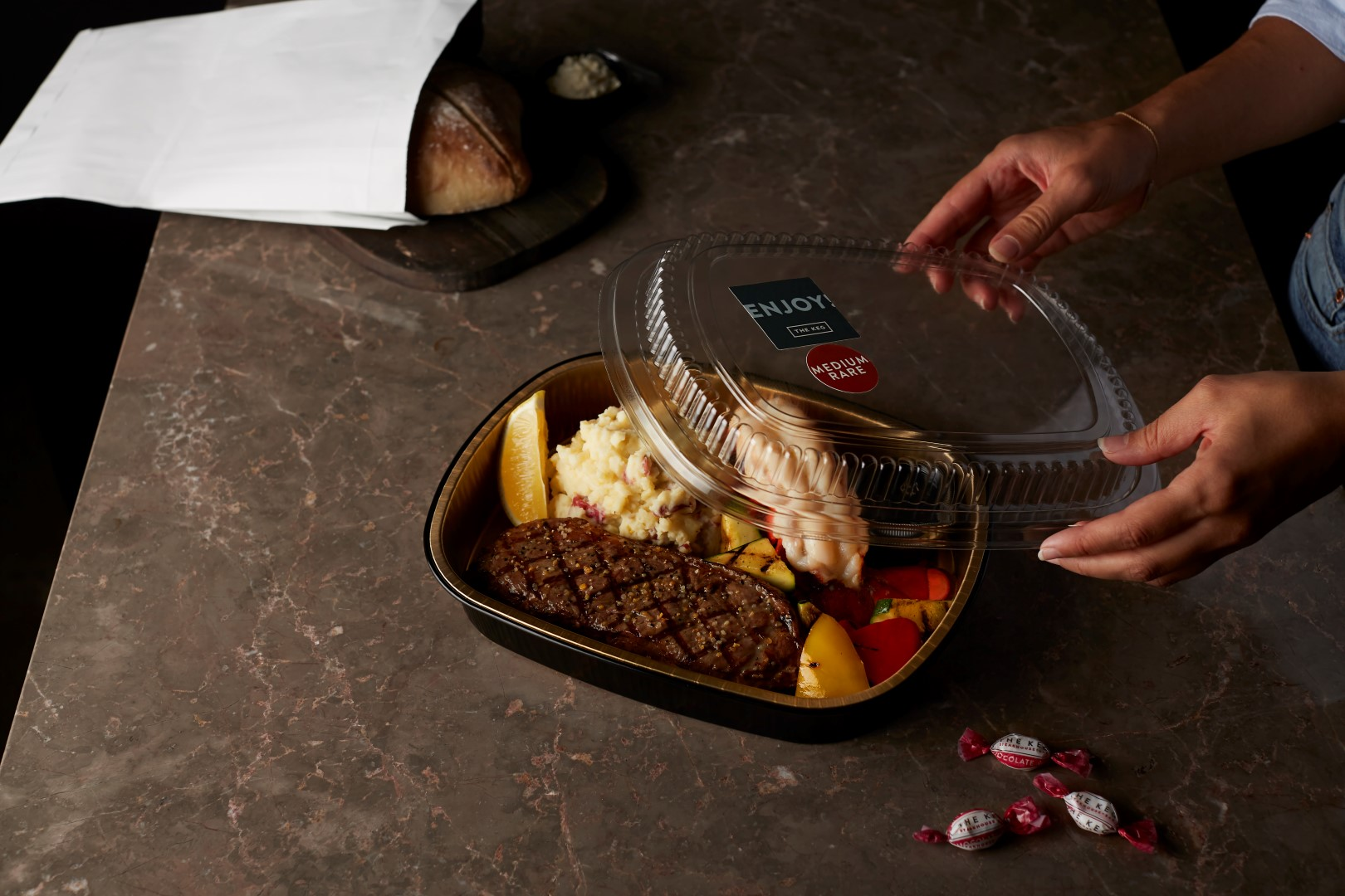 Takeout container with steak and lobster and hand holding cover