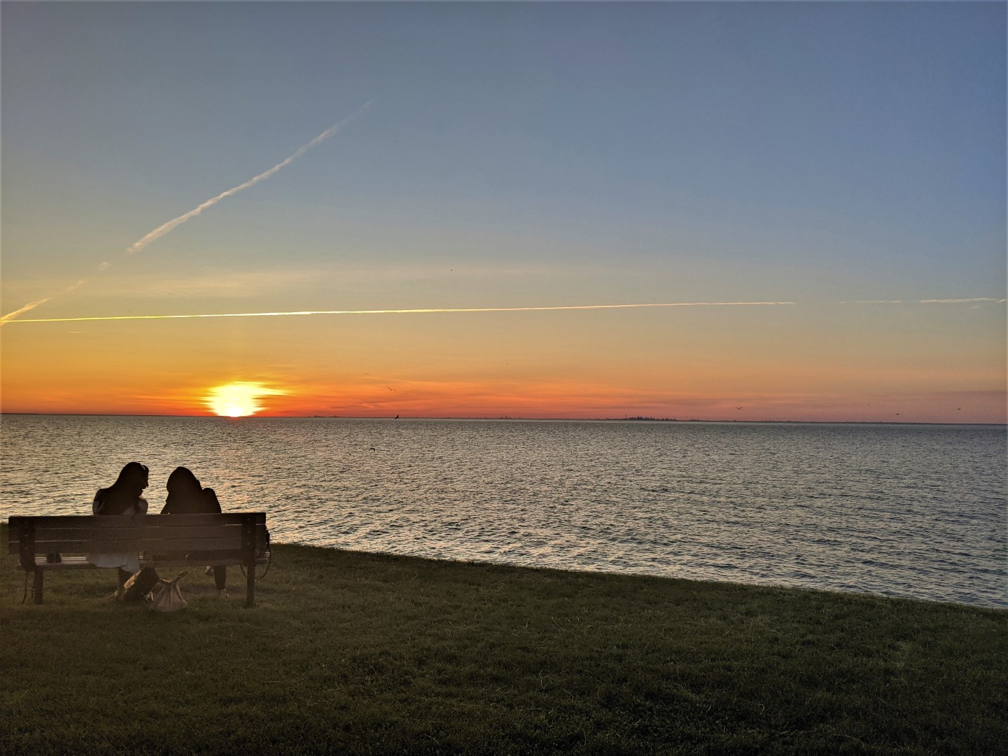 Two people shadows on bench watching sunset on the water