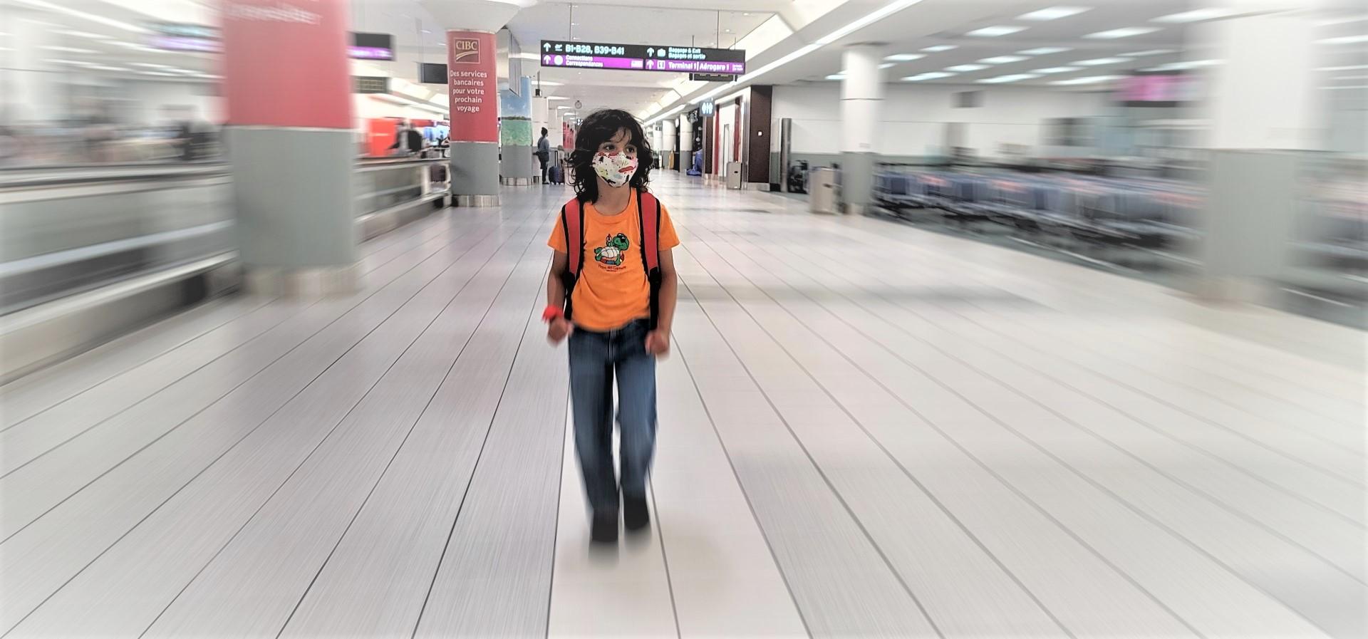 masked kid in orange shirt walking through airport