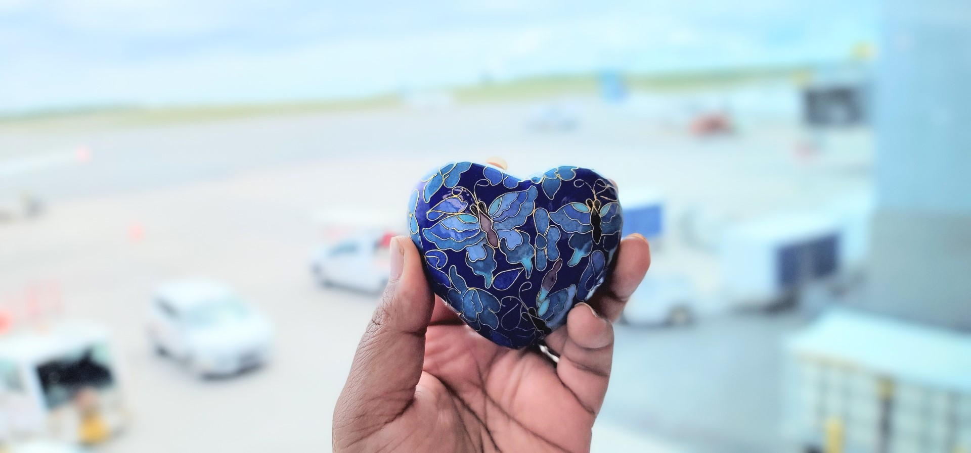 blue heart urn with ashes in hand