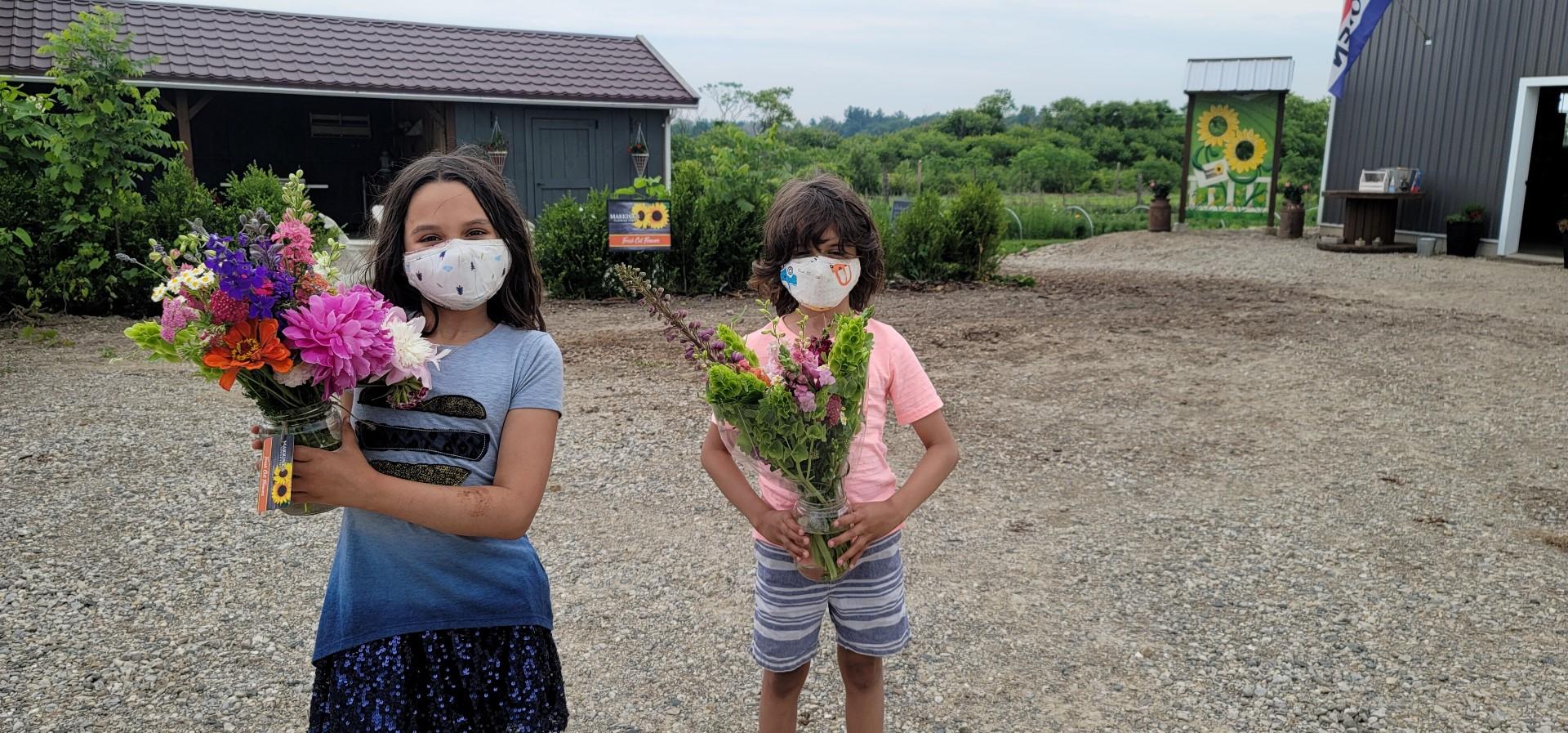 Masked kids holding flower bouquet