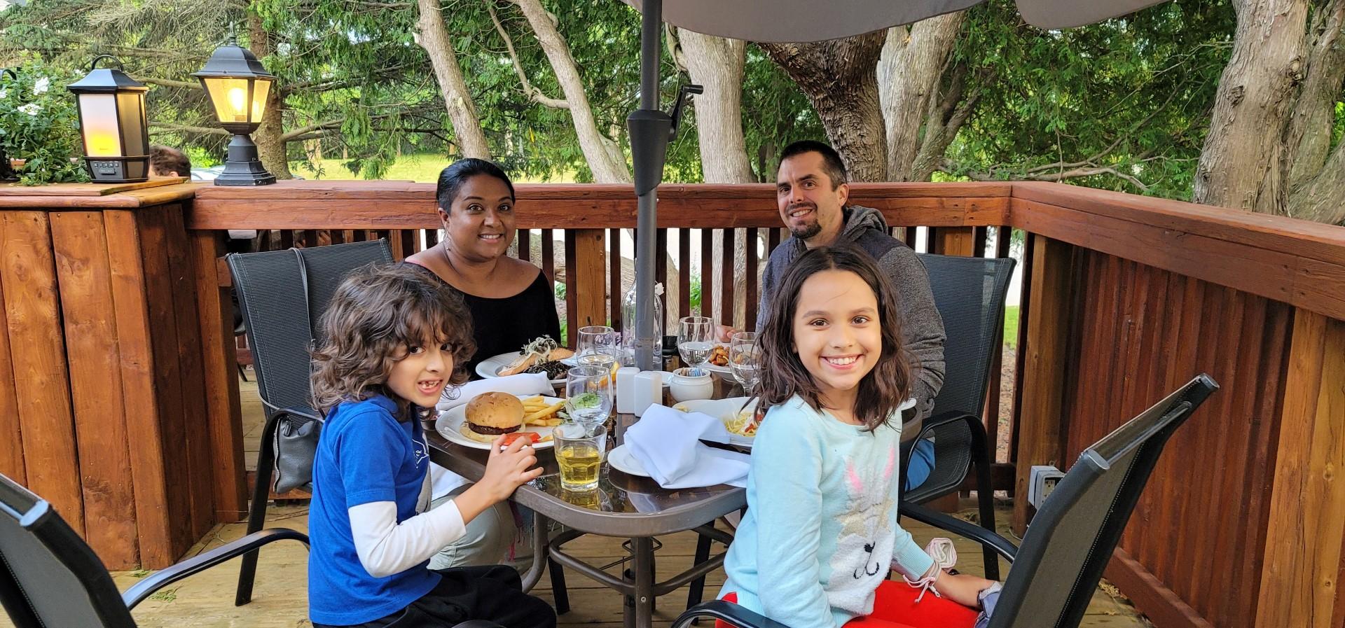 Mixed family enjoying dinner on a patio