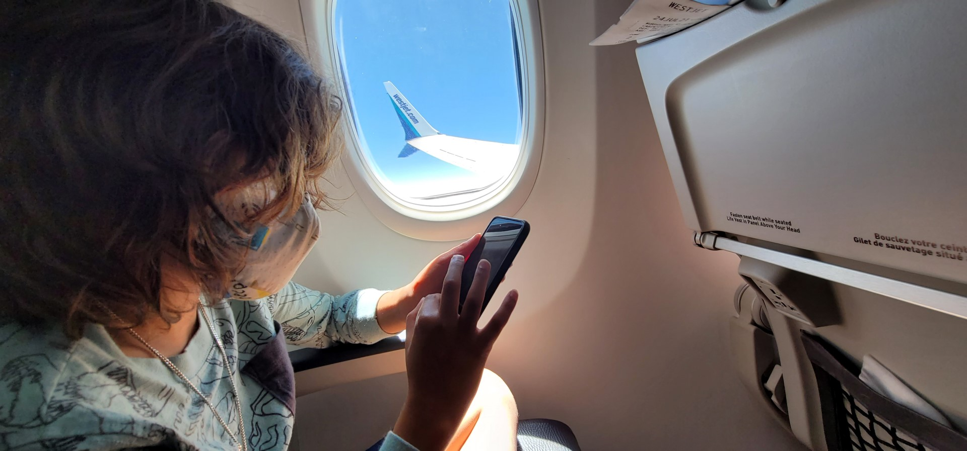 masked kid on plane near window