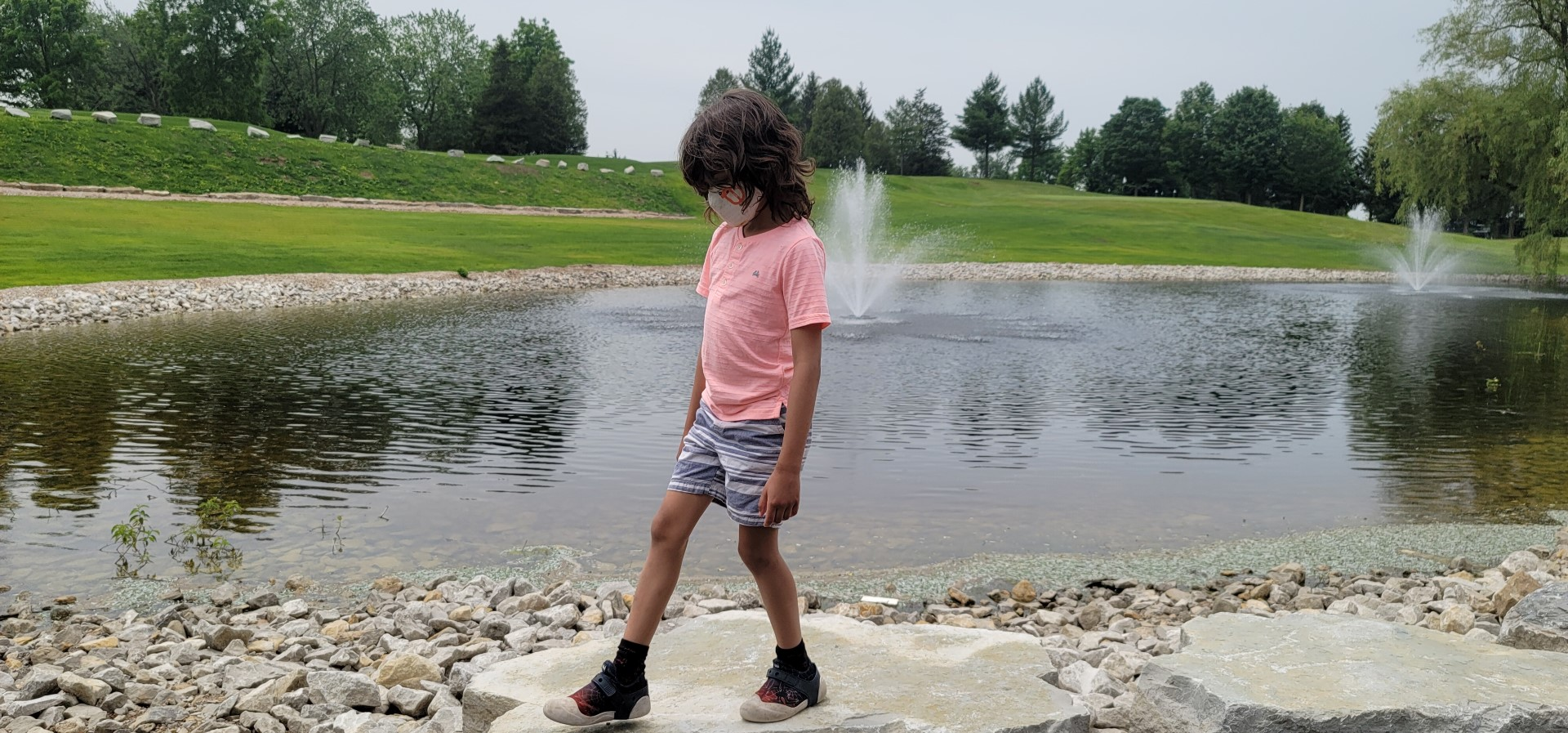boy wearing pink shirt and shorts walking by pond