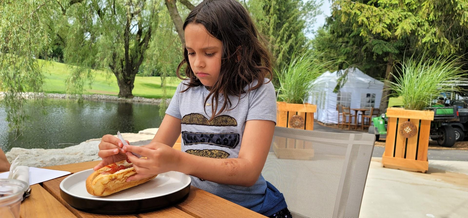 girl putting ketchup on hotdog