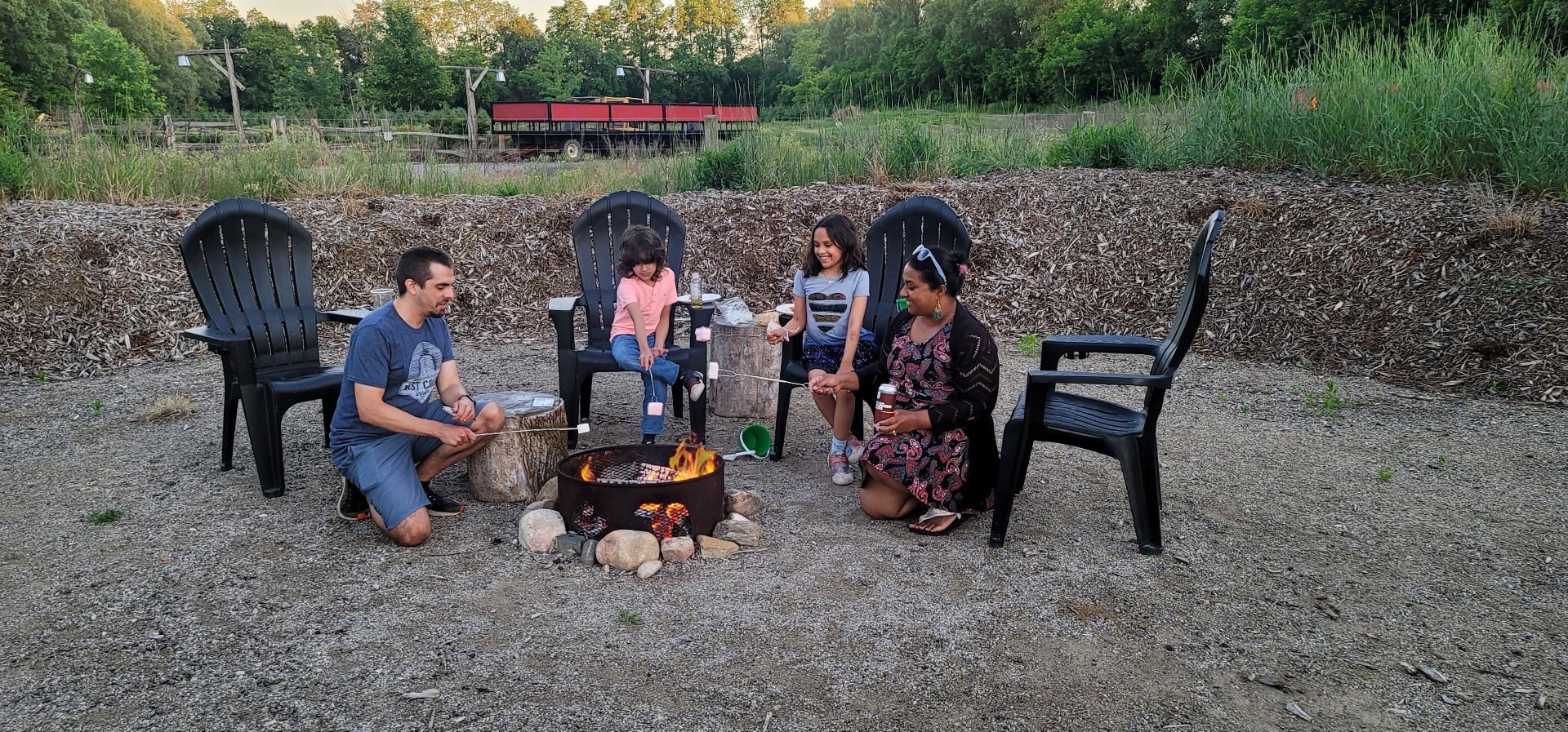 mixed Family roasting marshmallows over campfire