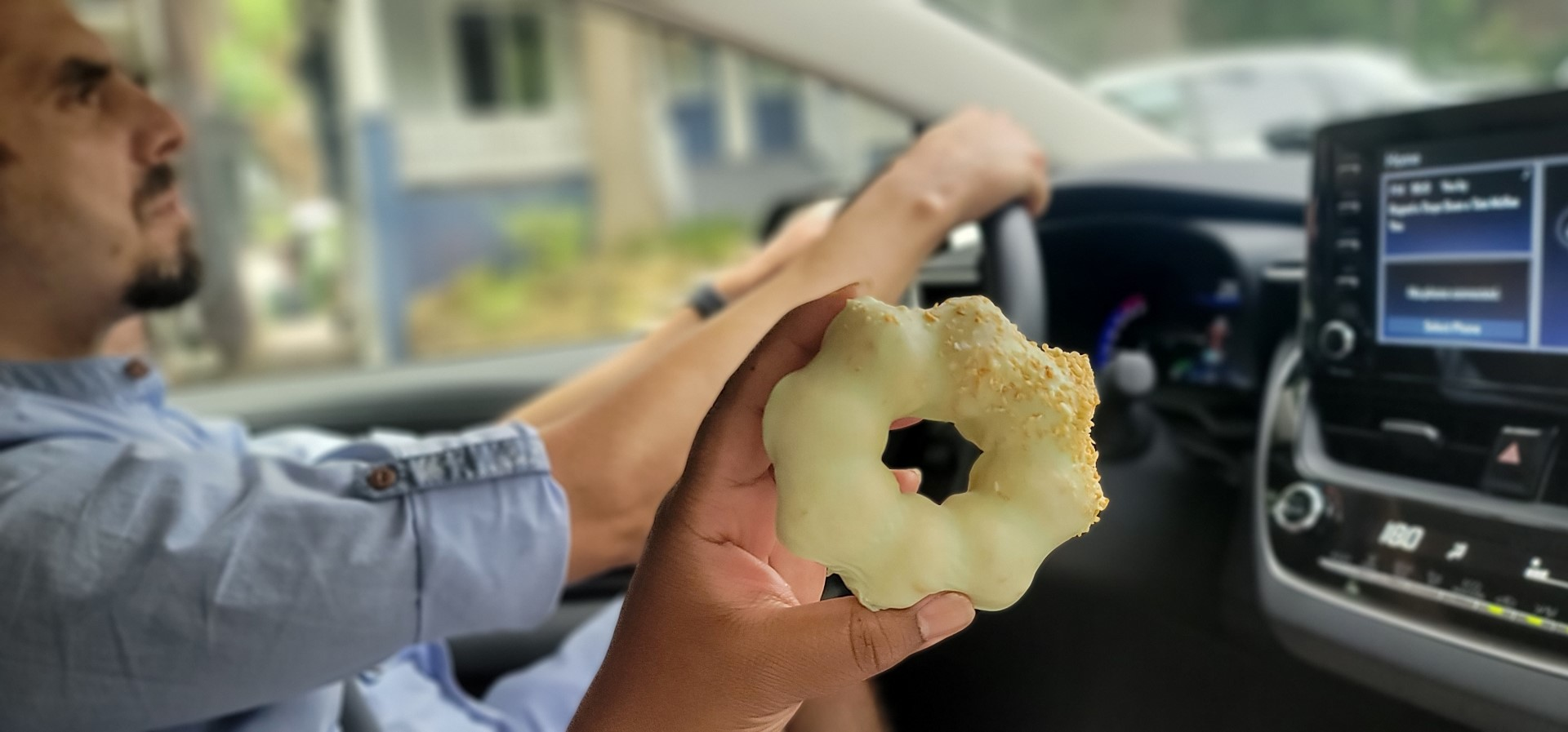 mochi donut in hand with another hand holding steering wheel