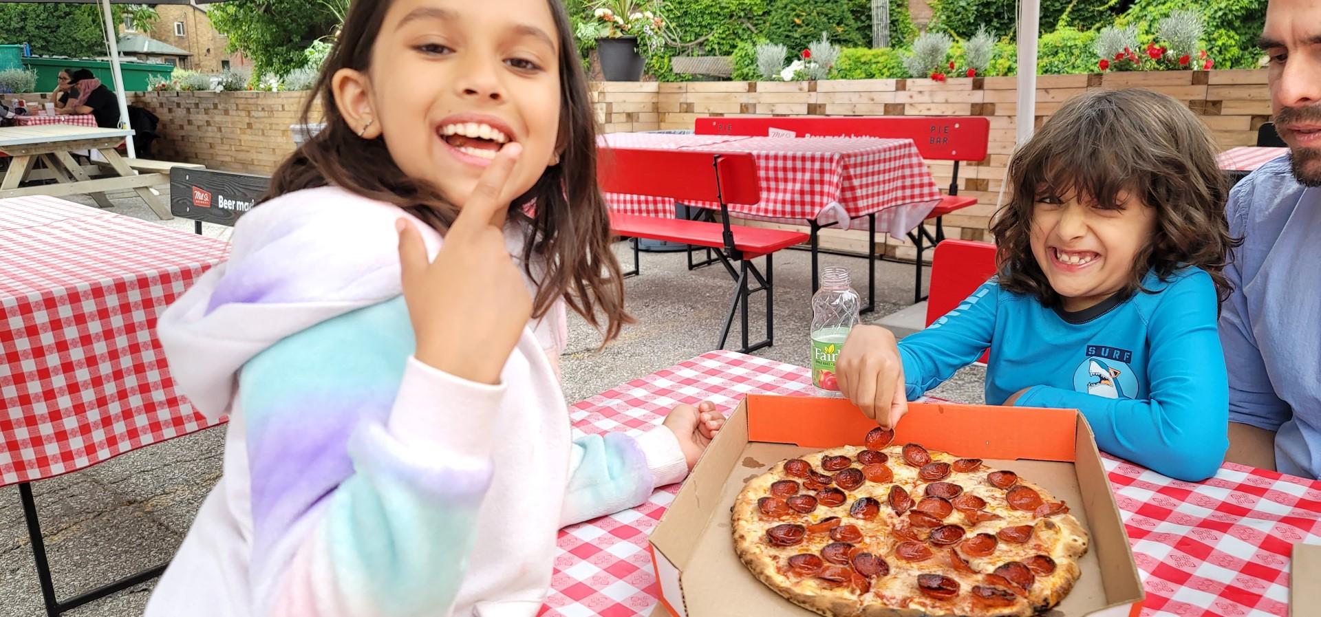 kids smiling eating Pizza