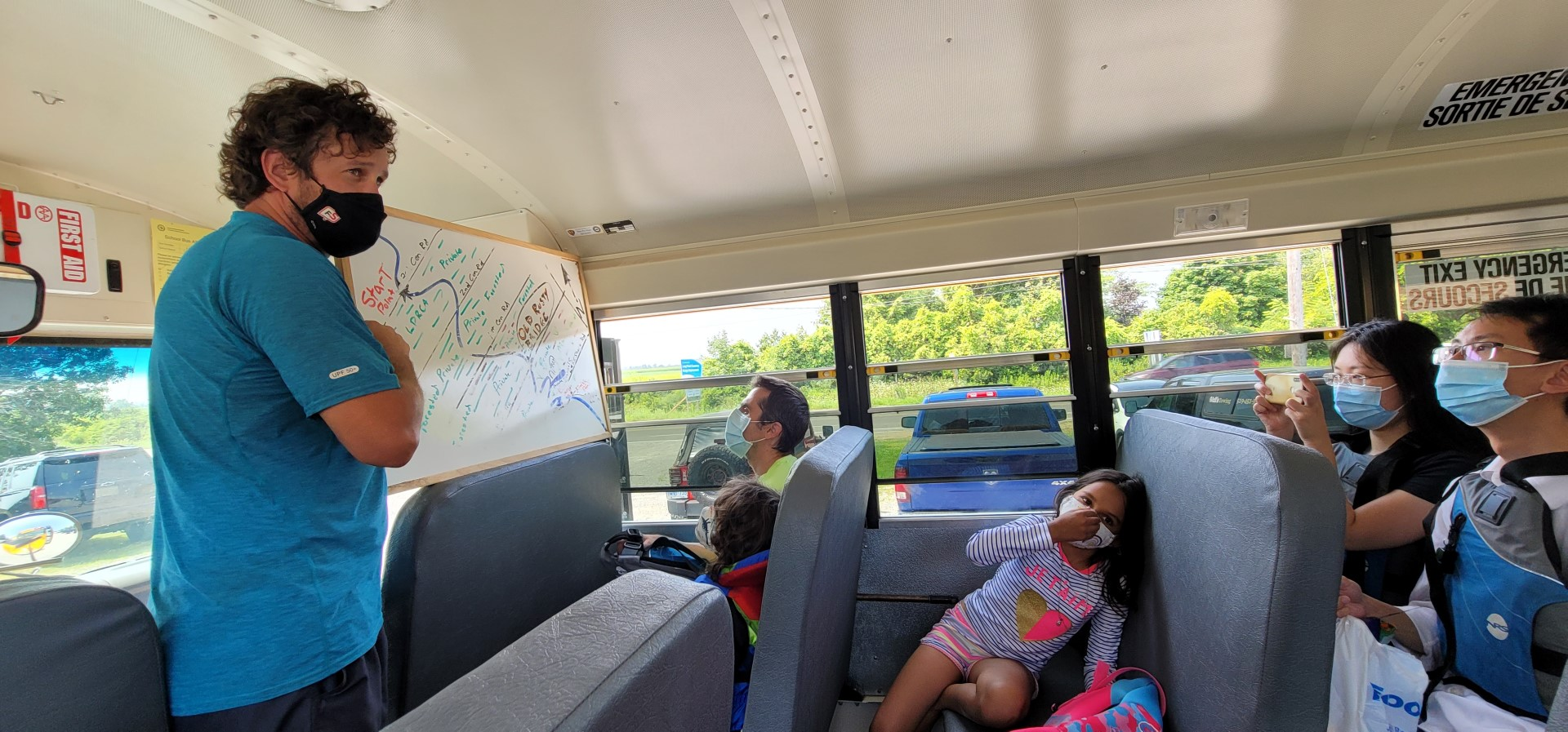 people on bus masked with instructor