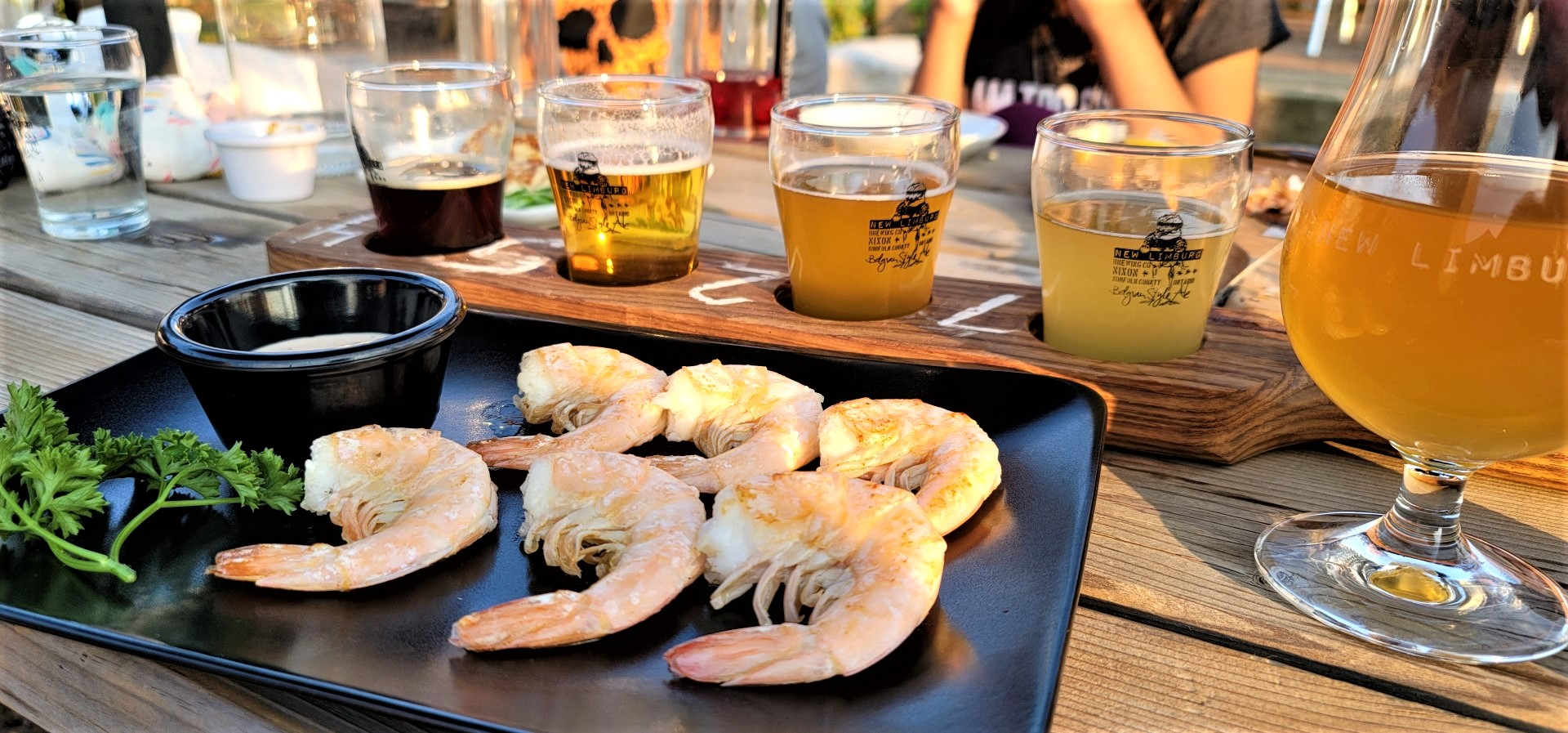 Grilled shrimp and beer flight on table