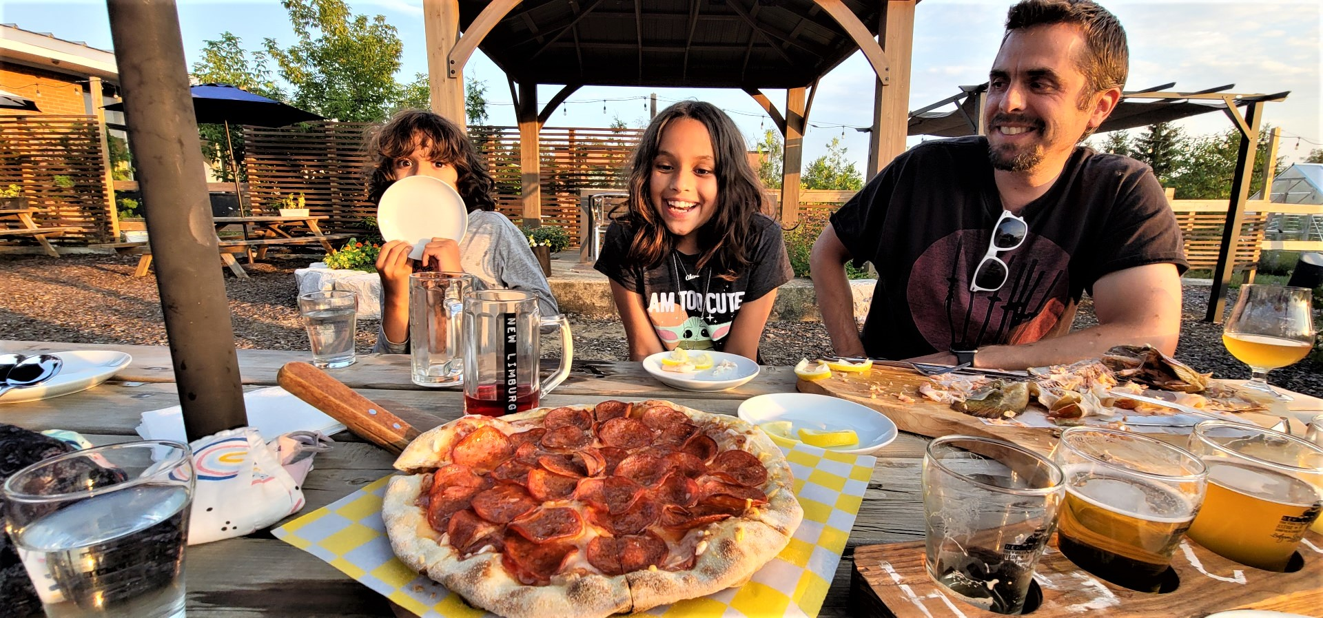 kids and dad smiling at pizza