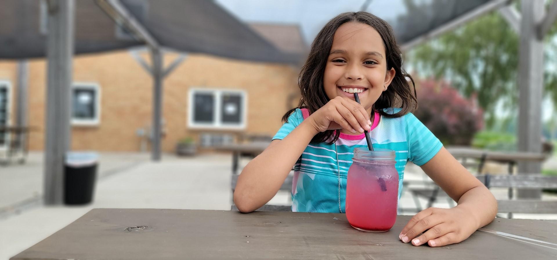 girl sipping blueberry lemonade