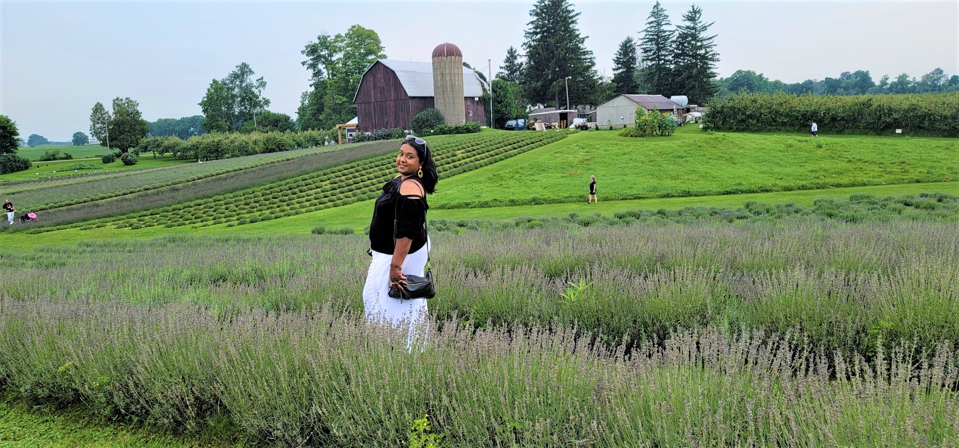 Yashy in lavender field with black top and white pants