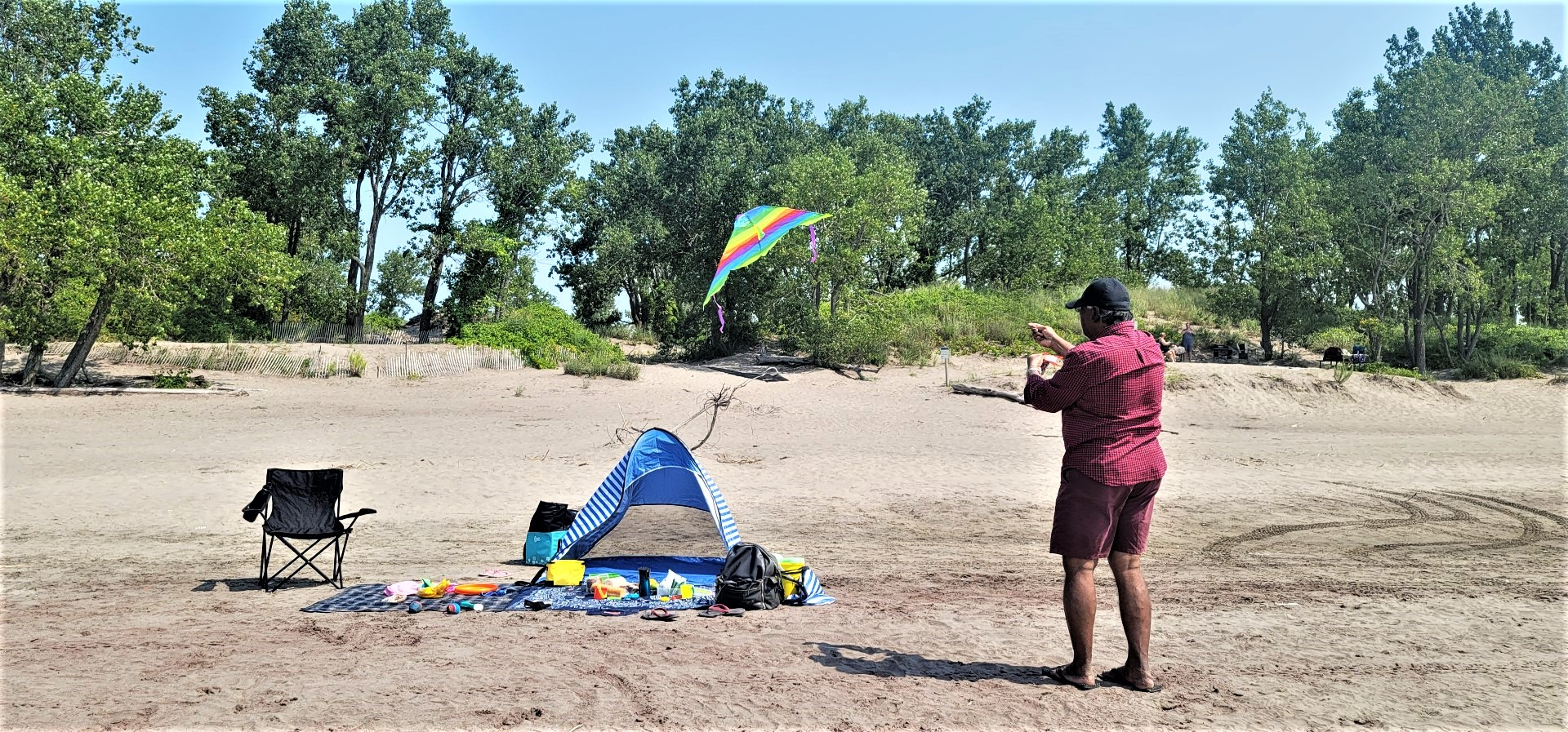 man flying kite at Long Point beach with blue tent and black chair