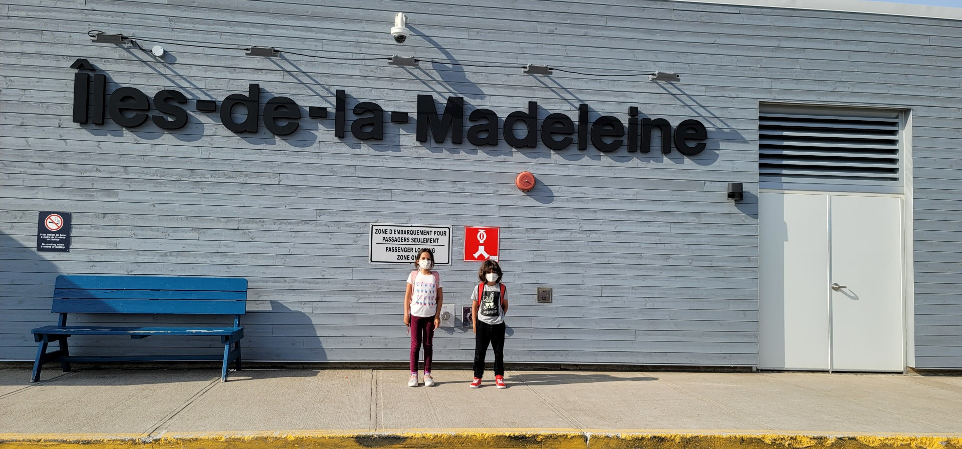 masked kids standing in front of Magdalen Islands airport