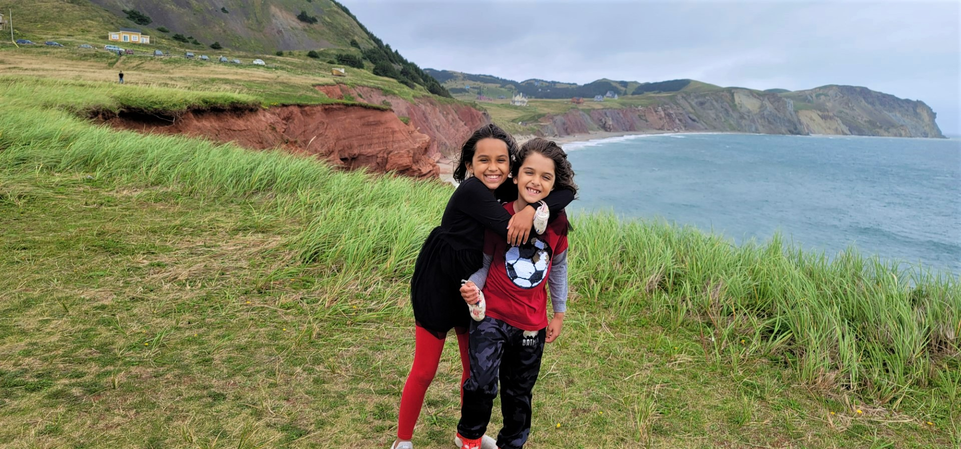 sibling hugging with wind blowing around them as they stand on a Magdalen Island mountain