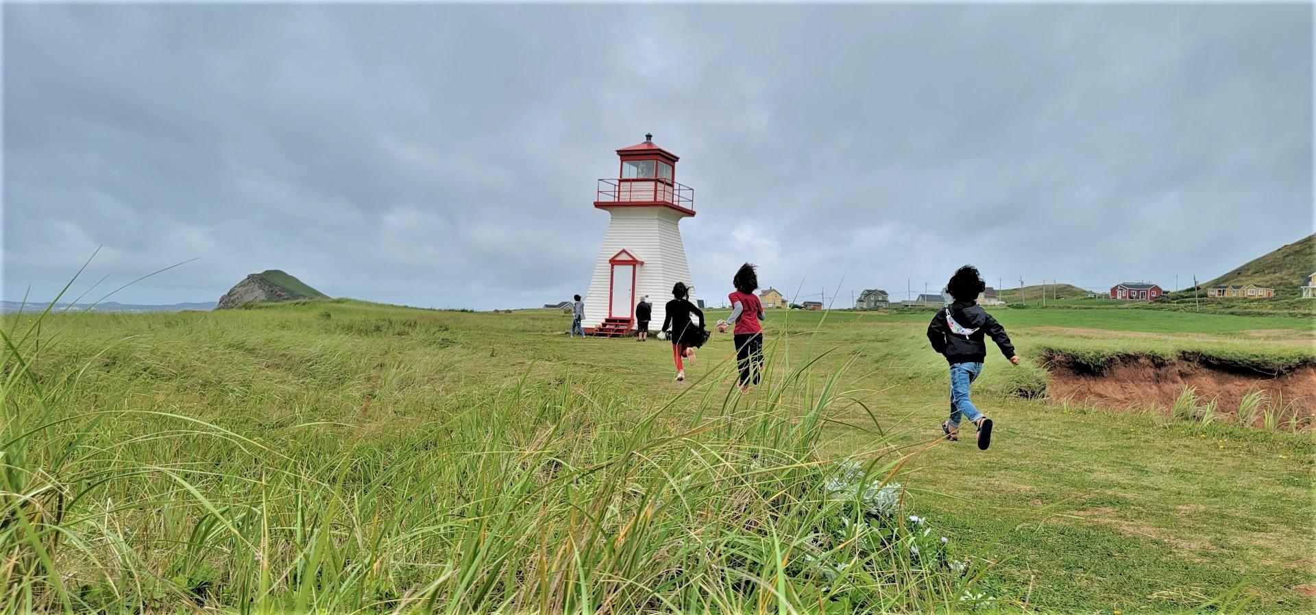 Kids running towards lighhouse on Magdalen Islands