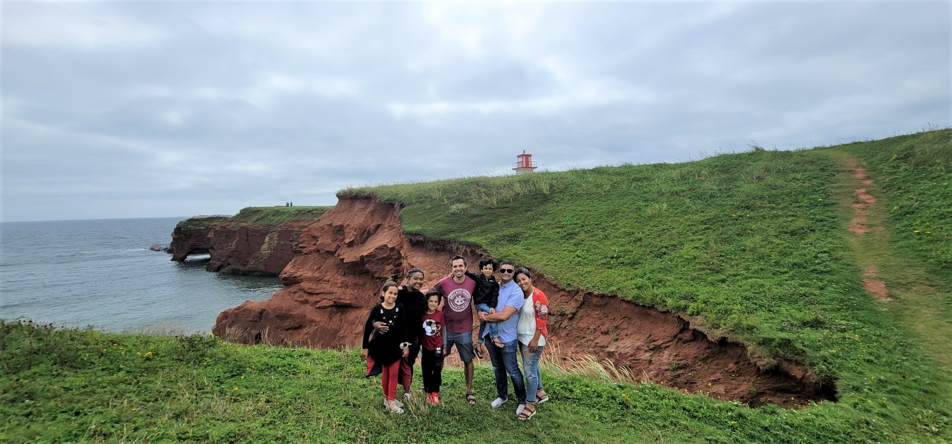 mixed family infront of lighthouse and red cliffs on Magdalen Island