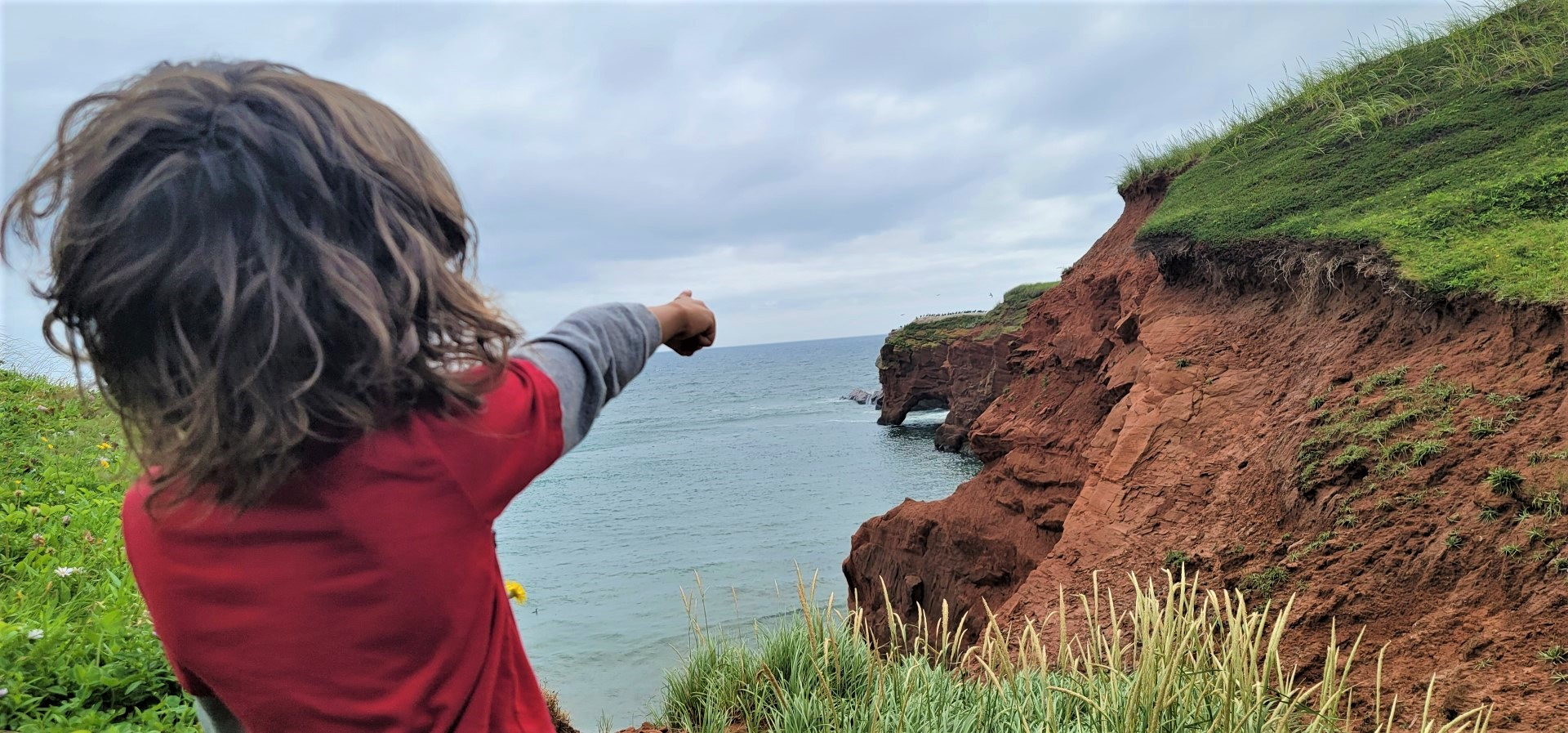 child in red shirt pointing at hills on Magdalen Islands
